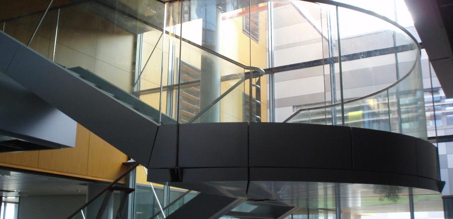 Escalier acier avec garde-corps vitré cintré dans un hall d'hôpital